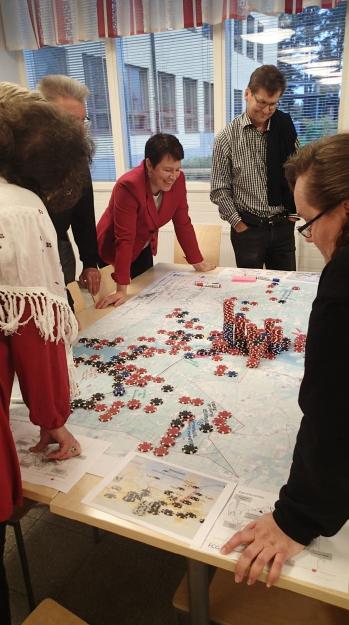 Valtuutetut ovat kokoontuneet tarkastelemaan pöydällä olevaa luonnoskarttaa, jonka päälle he ovat ryhmätöissä sijoittaneet väestön ja työpaikkojen lukumäärää symboloivia pelimerkkejä.
